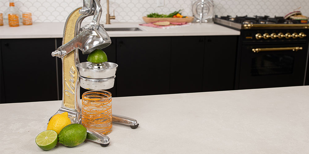 A standing metal juicer with citrus.