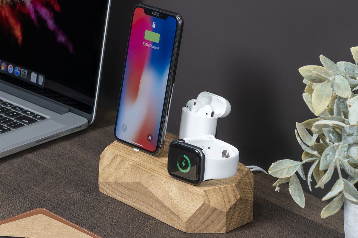 An Apple charging station, with an iPhone, AirPods and an Apple Watch
