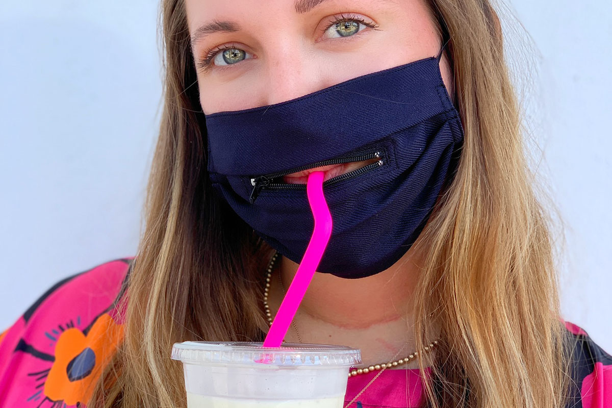 A person wearing a face mask with a zipper around the mouth, sipping a beverage.