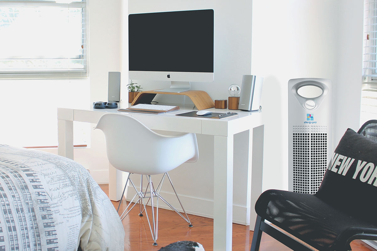 A room with a desk and an air purifier in it.