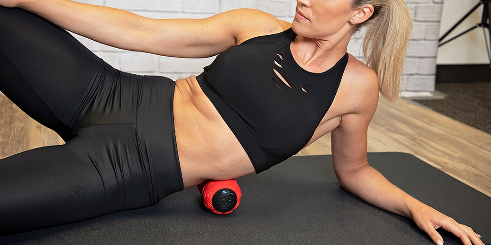 A person wearing fitness clothes using a rolling massager
