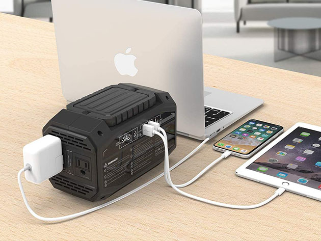 A portable power station connected to a laptop, phone and tablet