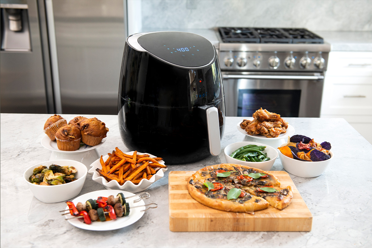 An air fryer with an array of food on a counter.