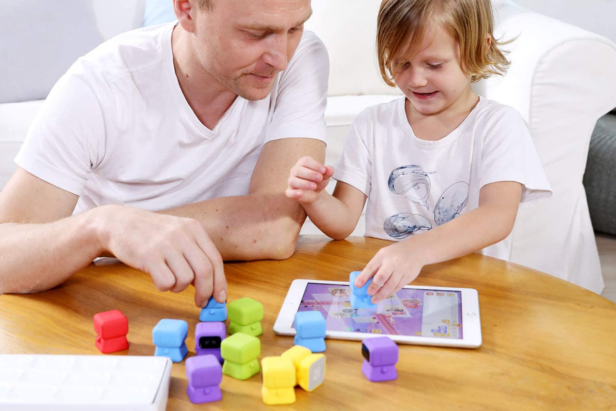 A parent and child playing an interactive coding game