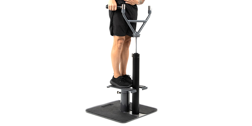 A person standing on a home gym and trainer.