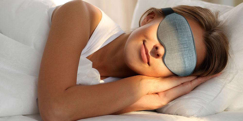 A person sleeping wearing an eye mask