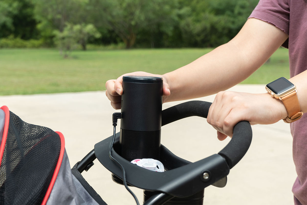 A person pushing a stroller, with an air purifier in it.