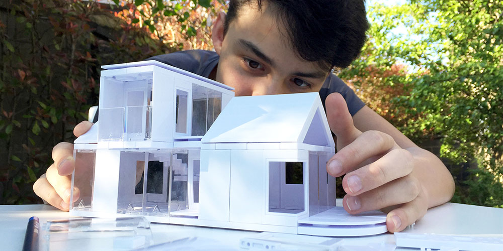 A person playing with an architecture model kit