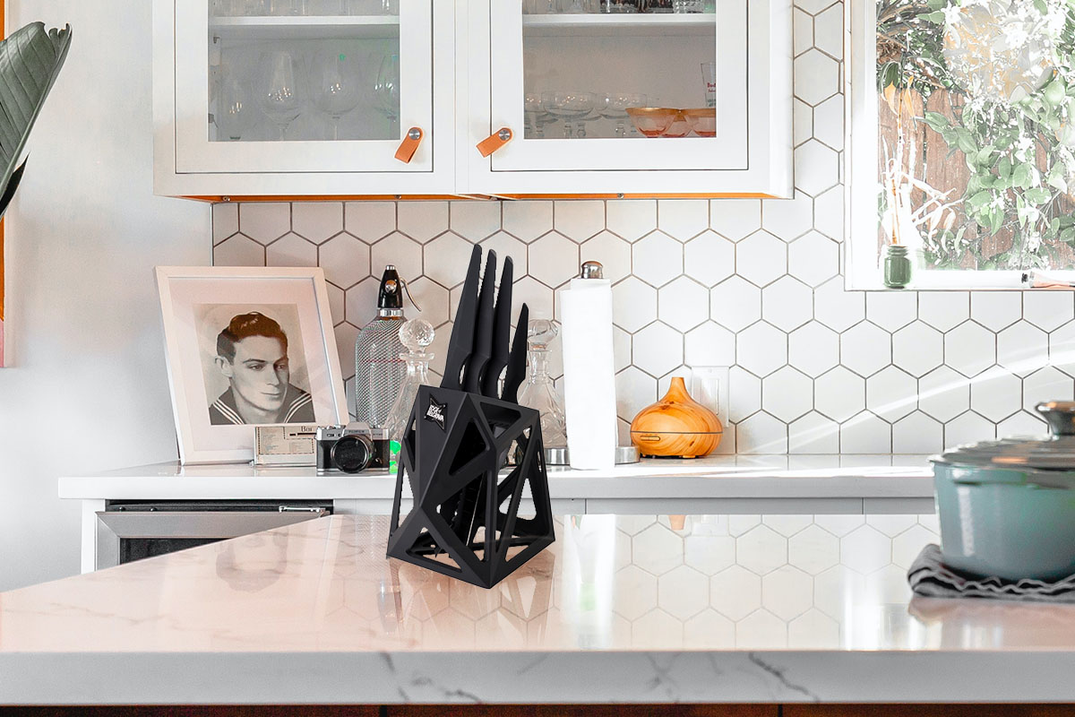 A countertop with a black knife block.