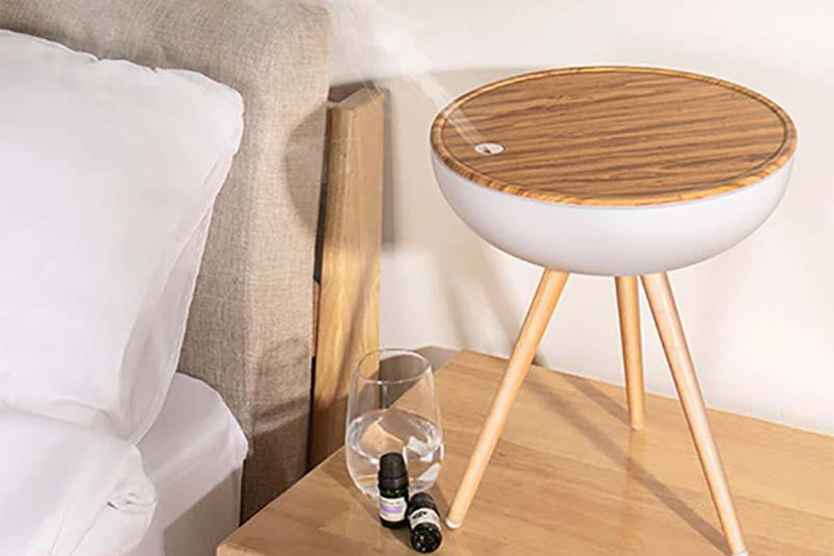 A diffuser on a nightstand next to a bed