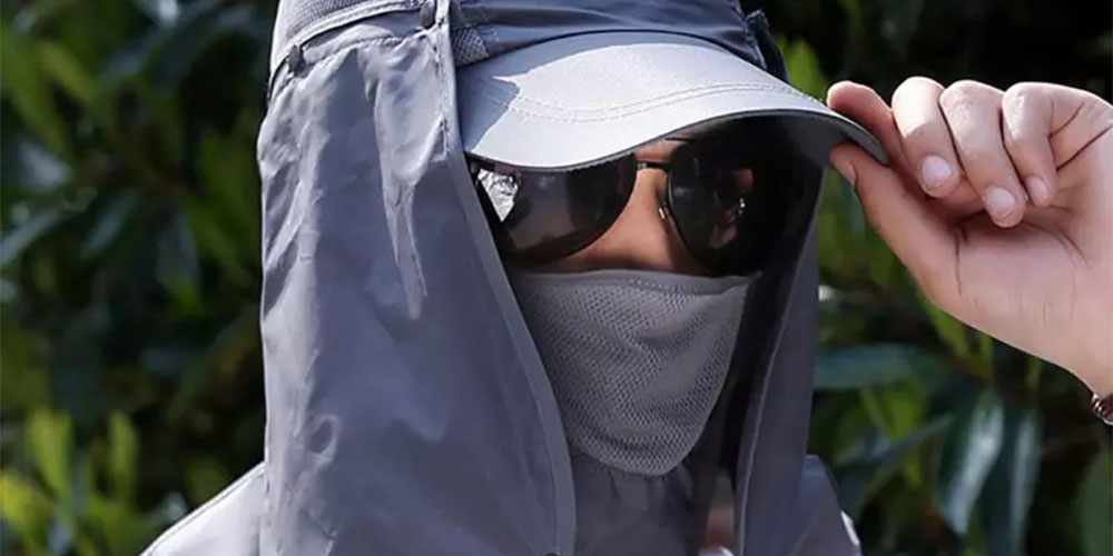 A person wearing a hood, cap and sunglasses