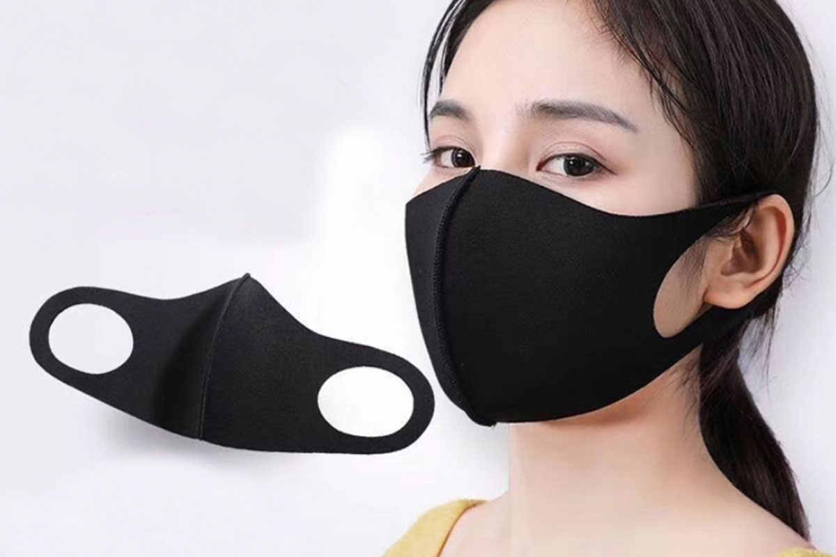 A person wearing a face mask, with another face mask to the side.