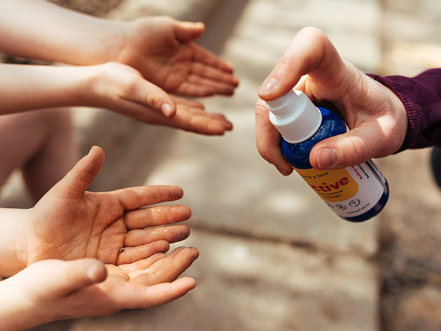 A person applying anti-microbial spray to two sets of hands