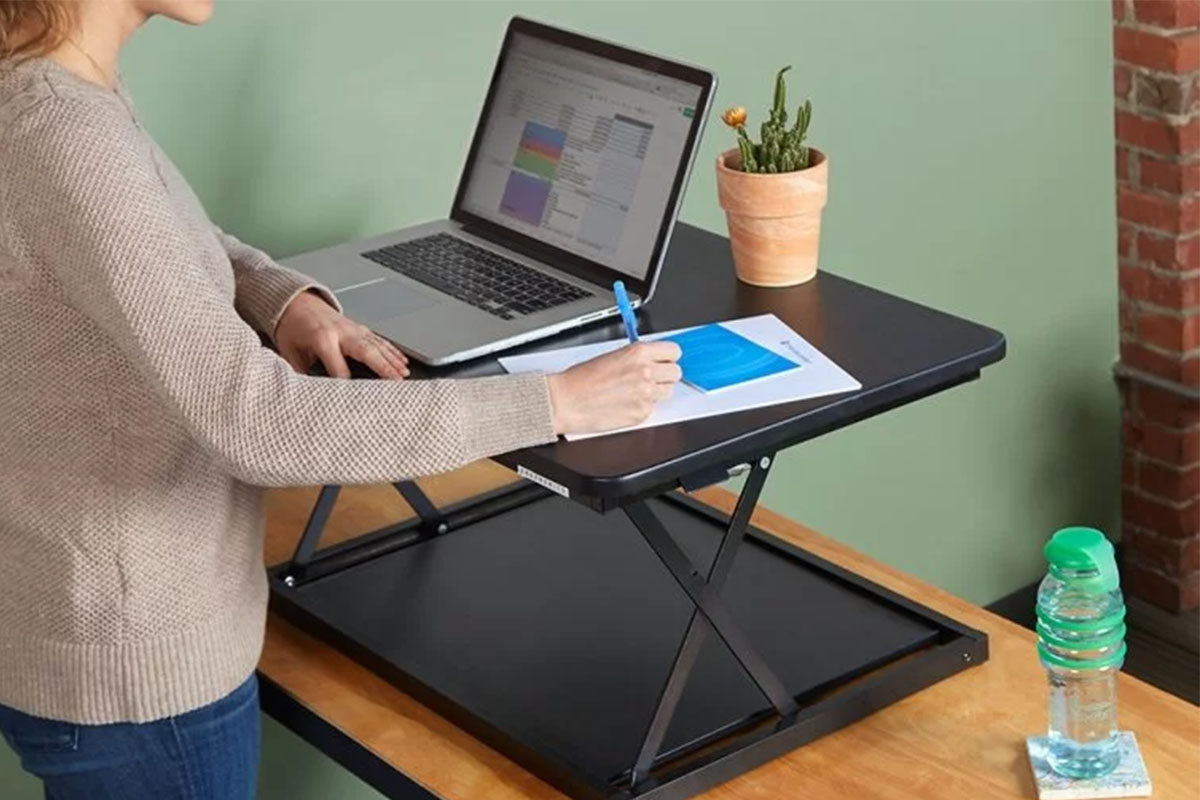 A person using an adjustable standing desk.